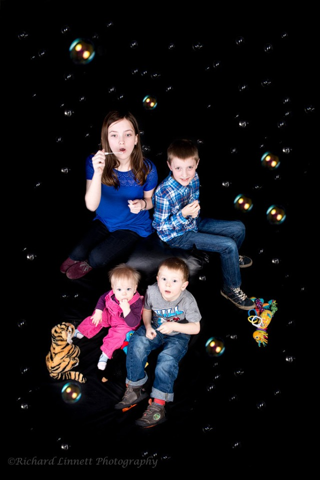 Studio portrait of children playing with bubbles