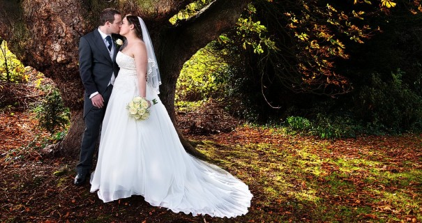 Newlyweds beneath the tree in Crabwall Manor gardens