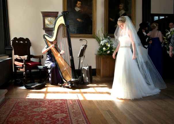 Young bride in window light listening to harp music