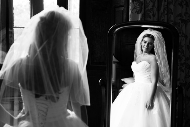 Beautiful bride looks into the mirror and wonders what the day will bring