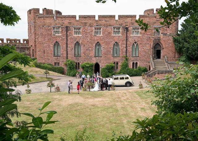 Wedding party enjoy drinks on the lawn at Shrewsbury Castle.