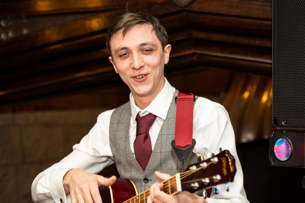 Groom entertains wedding guests with live music.