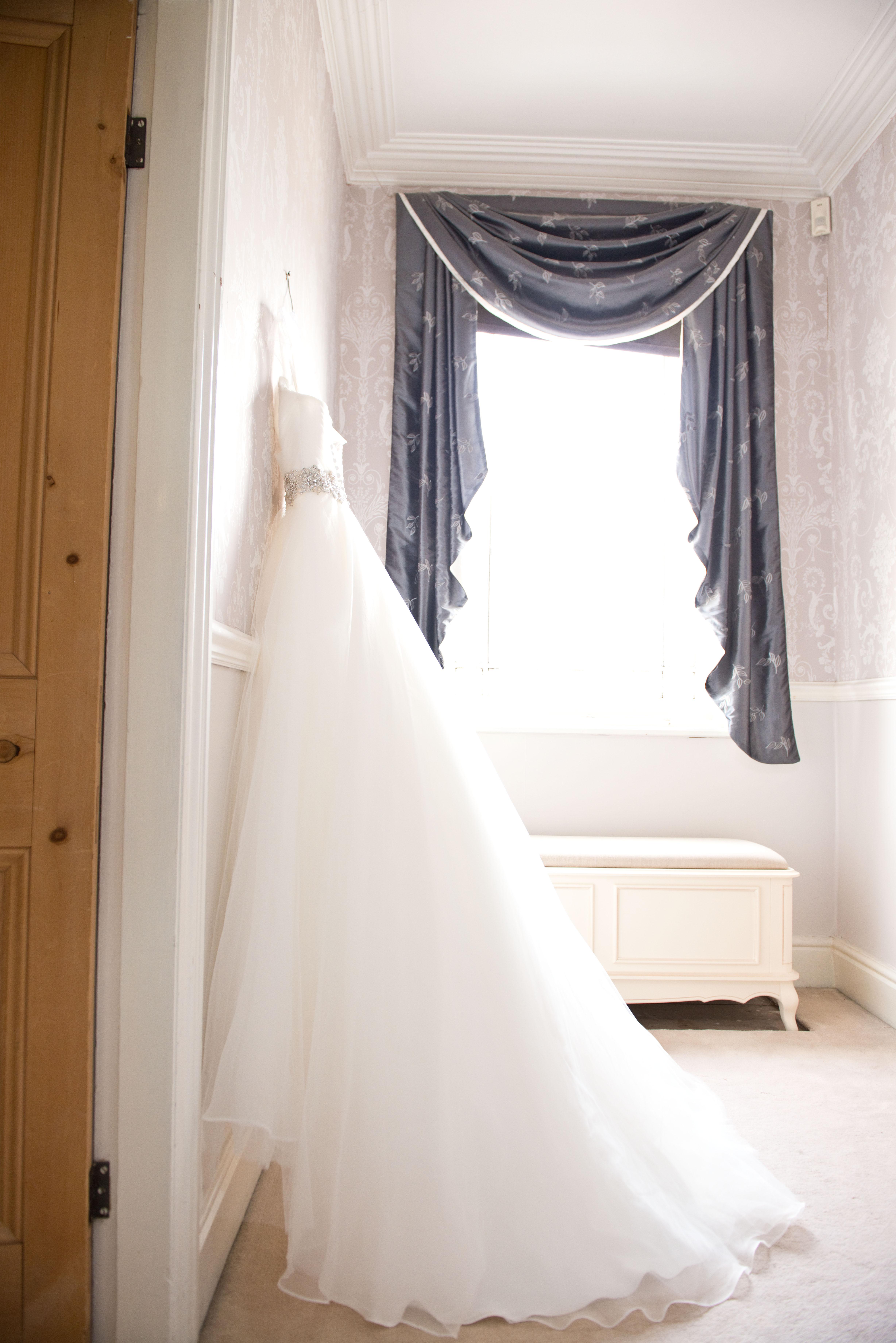 Wedding dress in window light, side-lit.