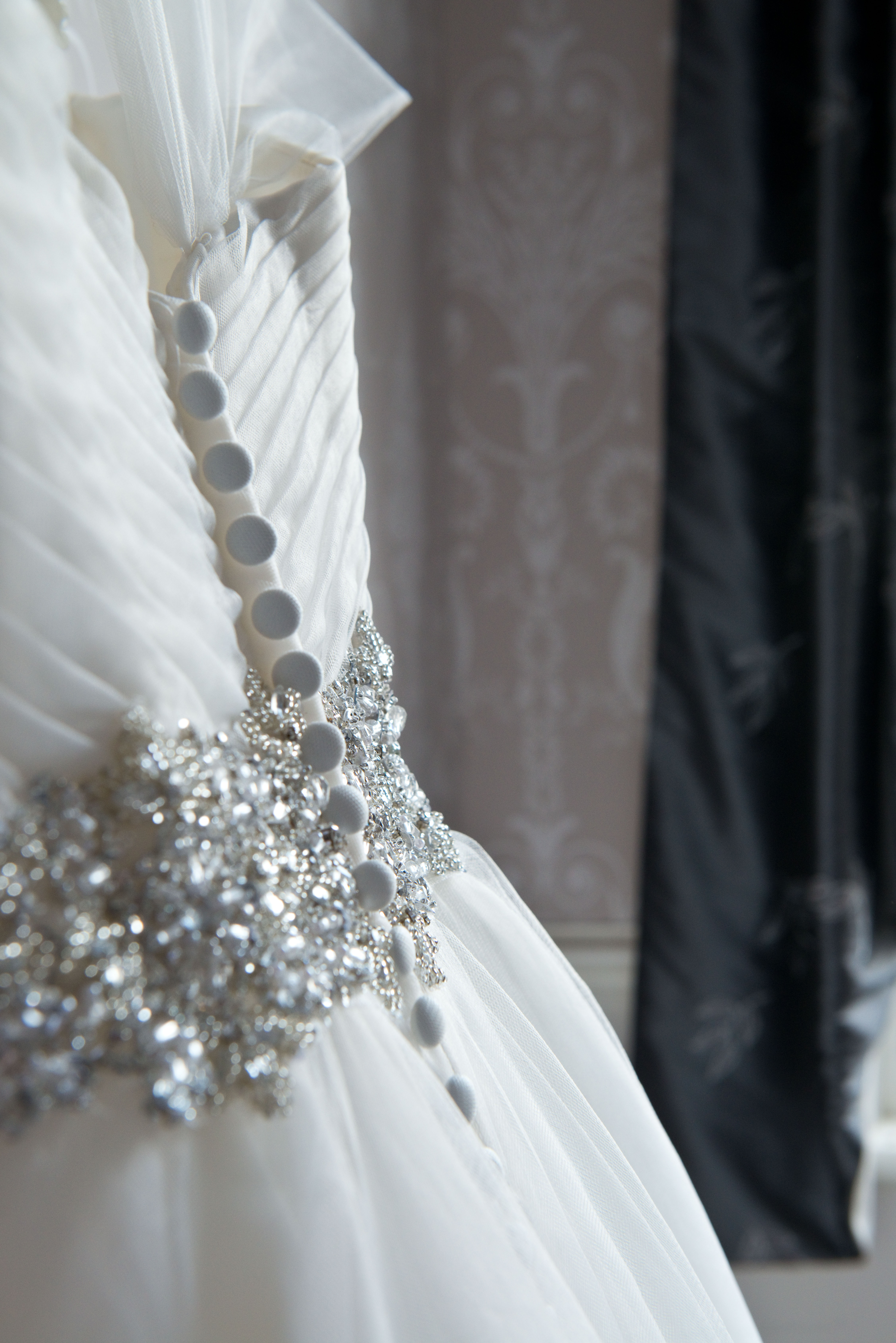 Wedding dress details in the sunlight from a window.