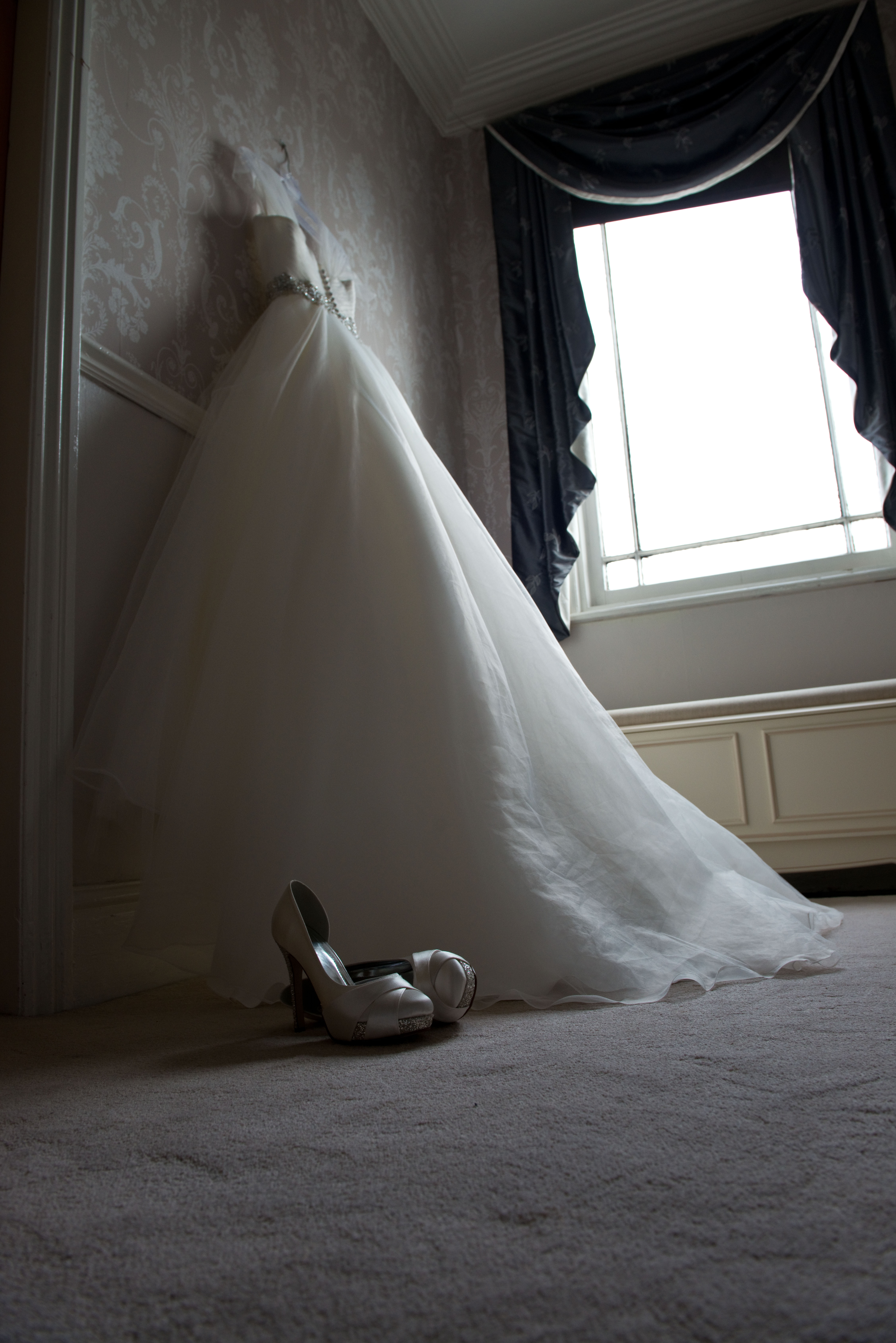 Lower key image of wedding dress with shoes in window light.