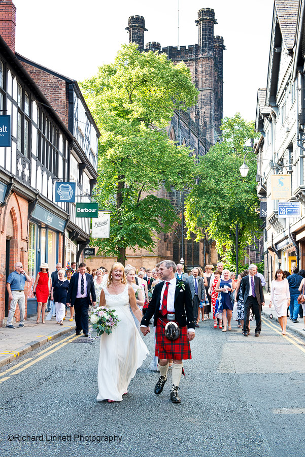 Wedding party walk the streets of Chester.