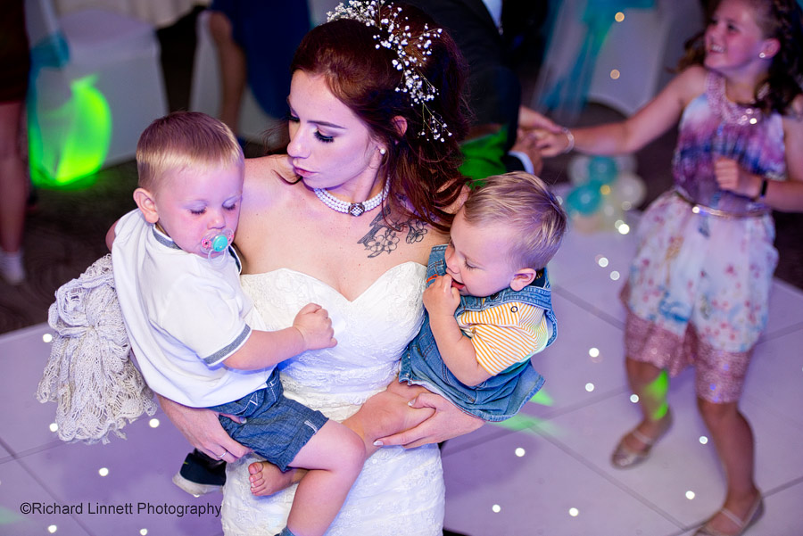 Bride dancing with her two young children in her arms.