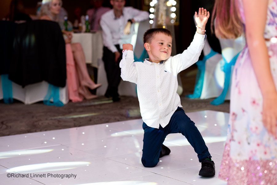 Boy shows off his dance moves at wedding reception.