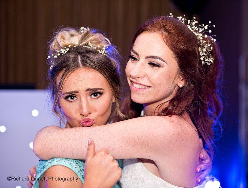 Bride and bridesmaid hugging and dancing.