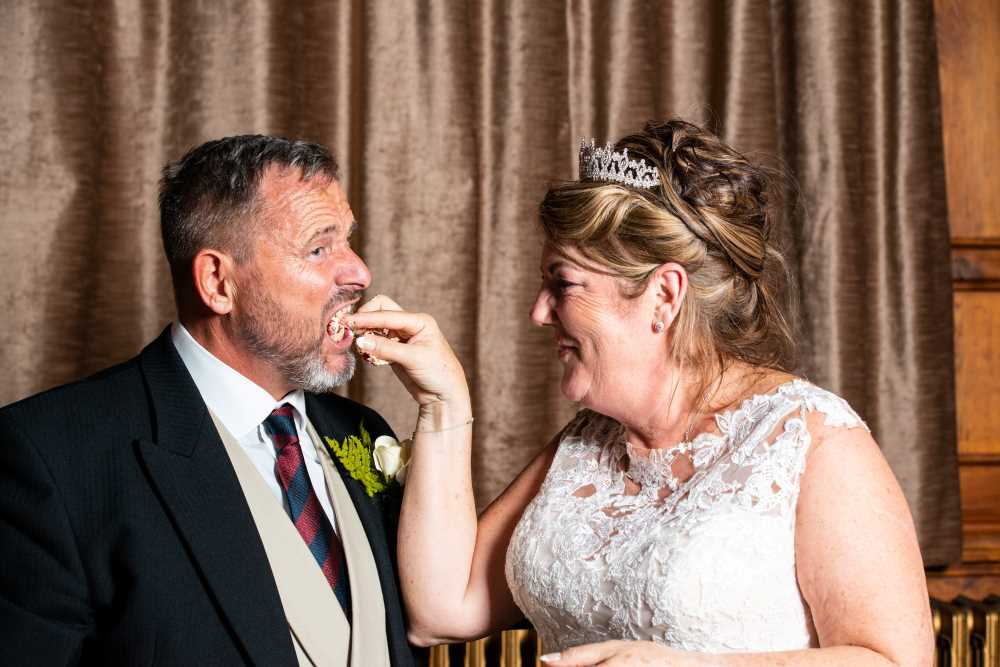 Bride feeds groom wedding cake at Chester Town Hall wedding.