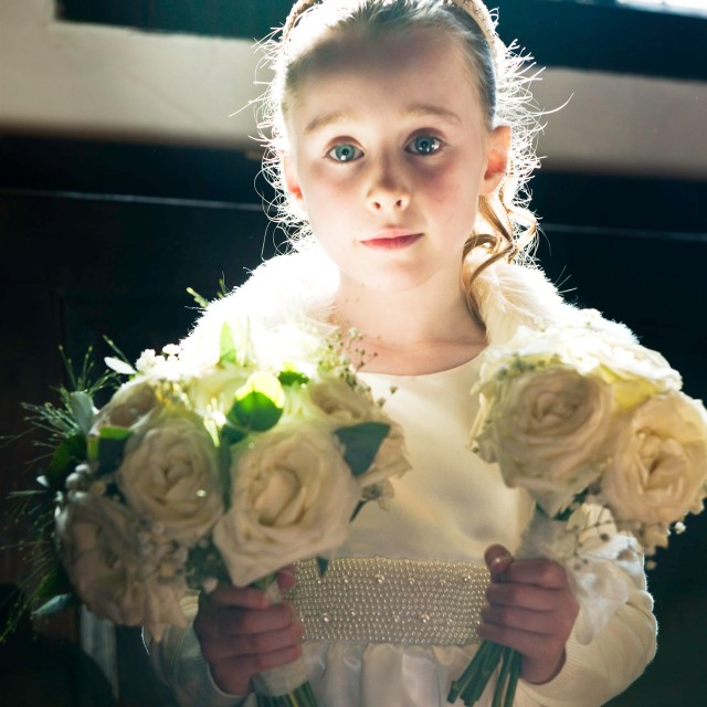 Young bridesmaid in church window light.