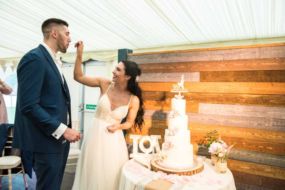 Bride and groom cut and eat cake at Plas Isaf.