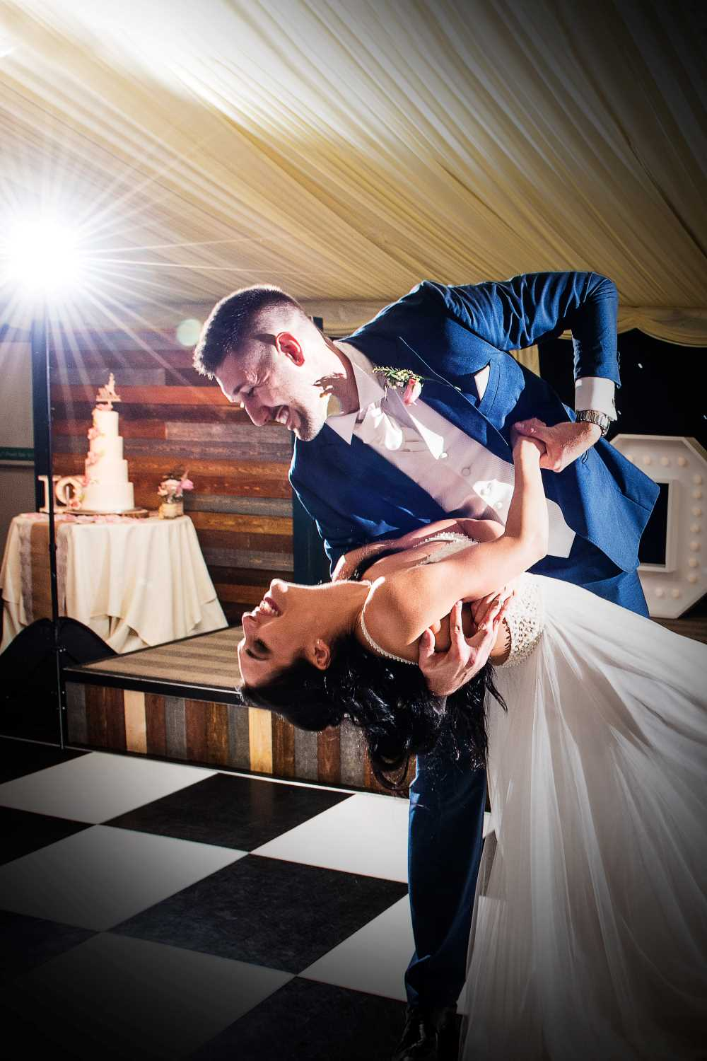 Groom dips bride during wedding night first dance.