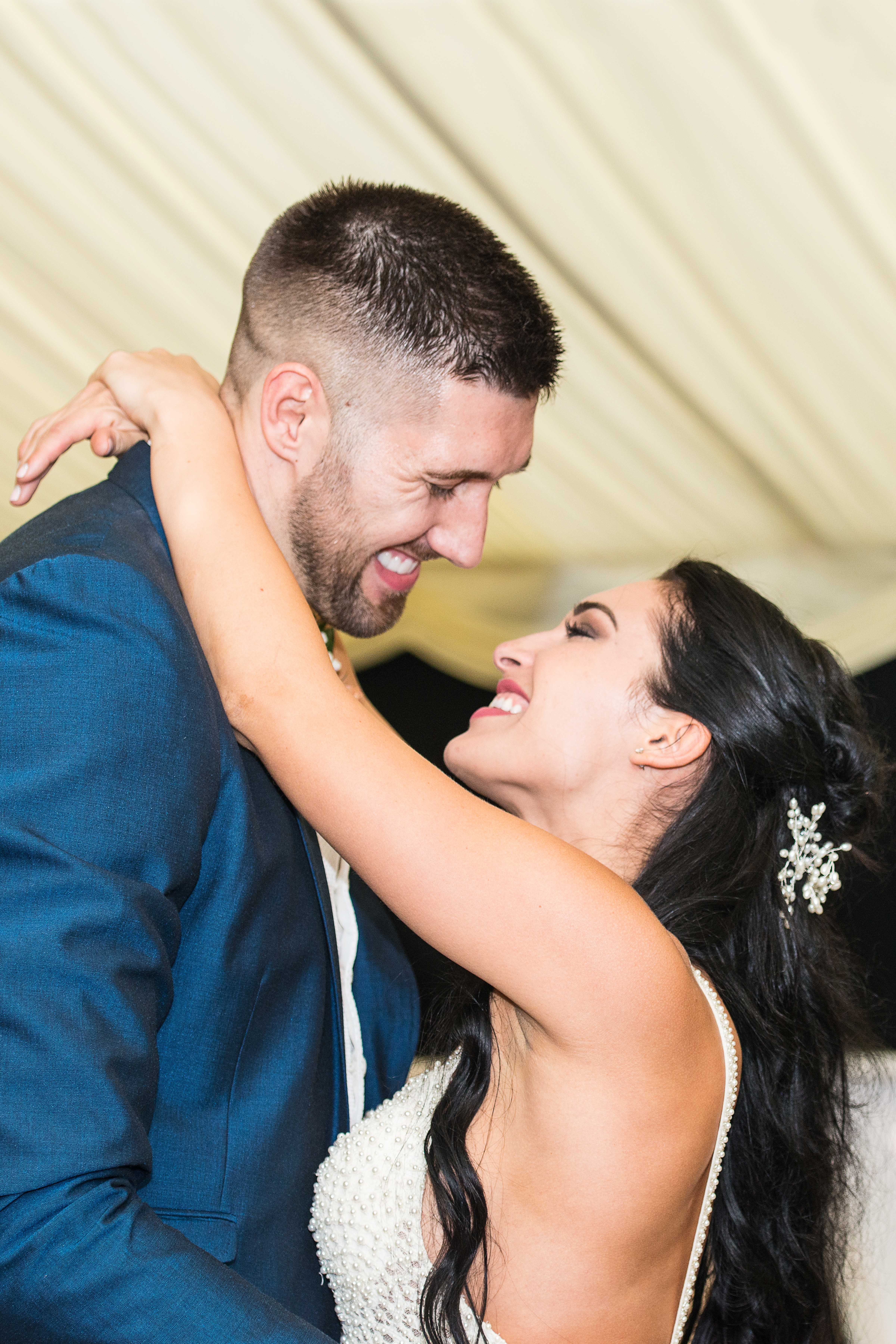 Newlywed couple make eye contact with each other during the first dance.