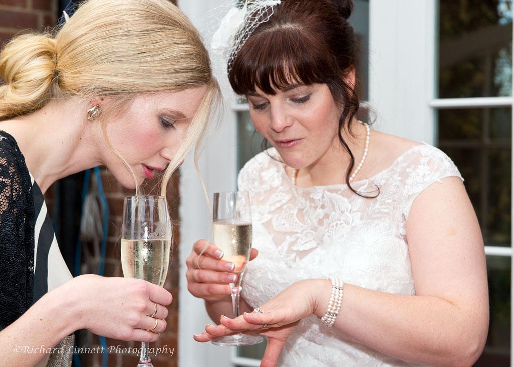 Bride shows friend her wedding ring.