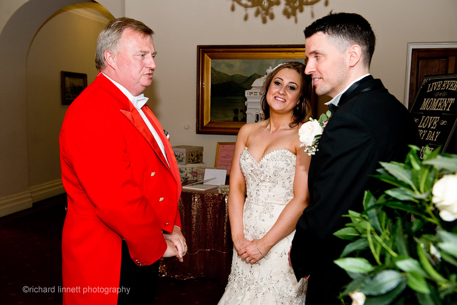 Bride and groom wait with the Toastmaster before entering the wedding breakfast.