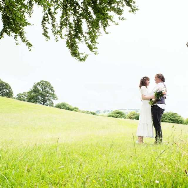 Bride and groom face each other and hug on footpath to bridge over the River Alyn.