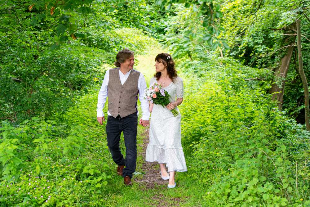 Bride and groom walk up country footpath together and exchange looks..