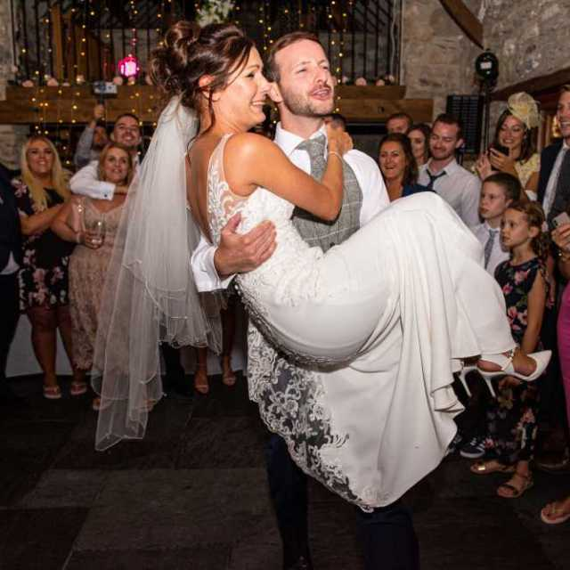 Groom lifts bride during first dance.